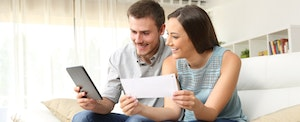 Happy couple checking their credit scores on a tablet