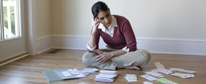 Woman sitting on floor, looking at bills and receipts