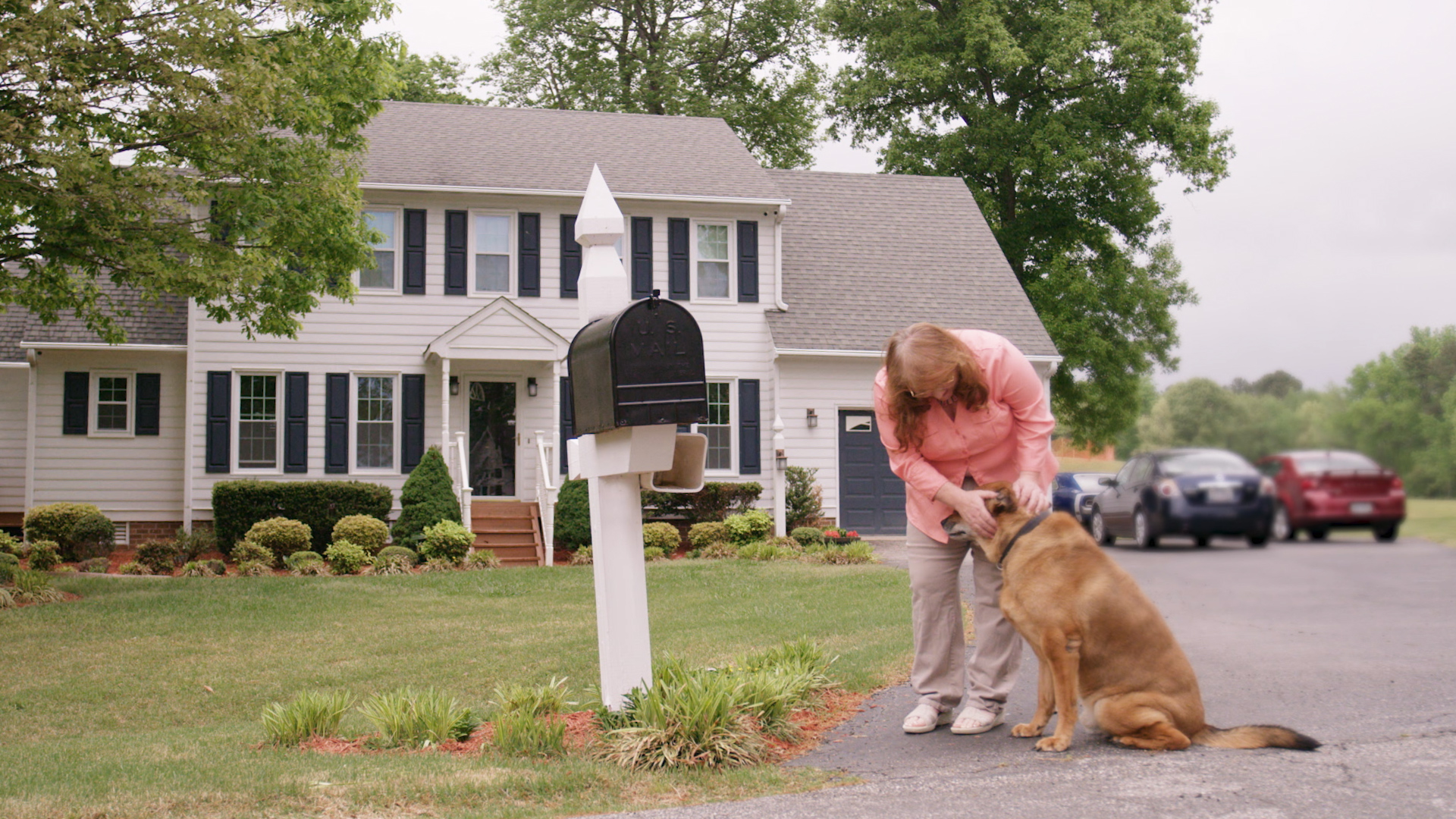 Donna pets her dog outside her new home