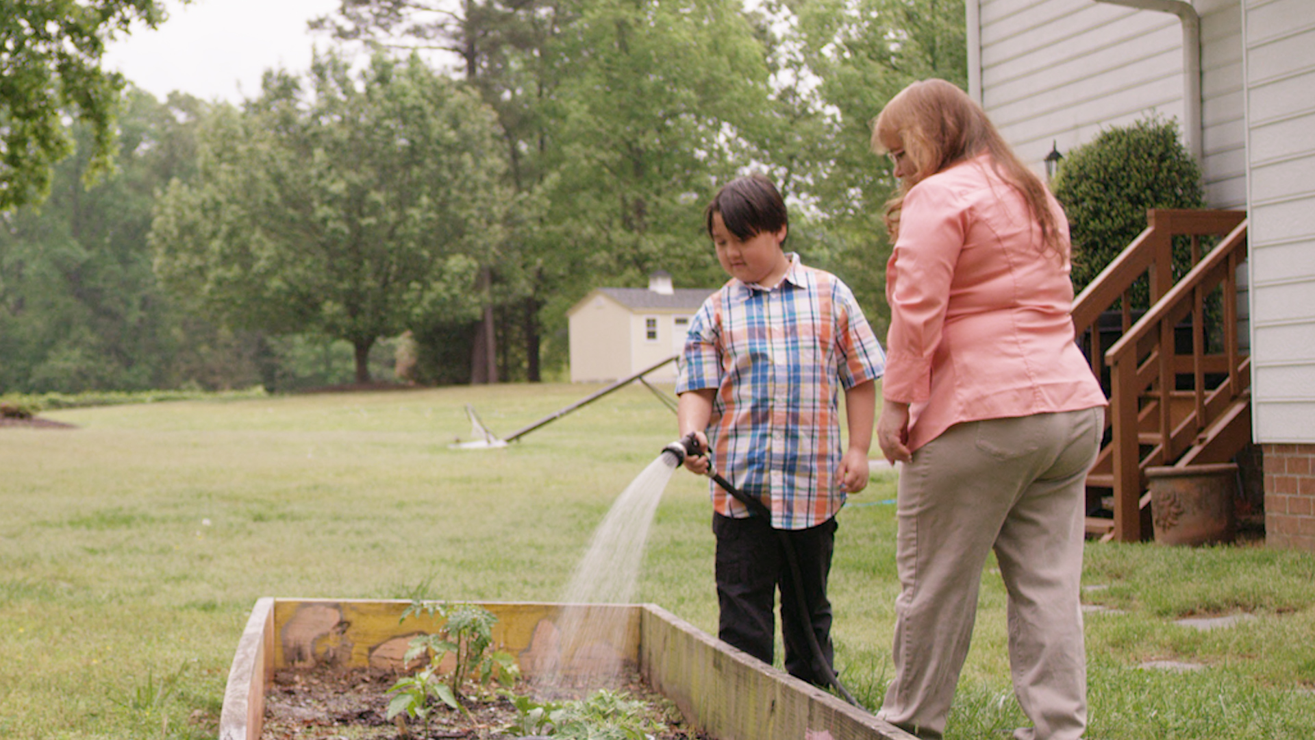 Donna and her grandson water the garden
