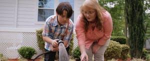 Donna helps her grandson tend the garden