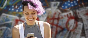 Smiling young woman with purple hair using her smart phone against graffiti wall