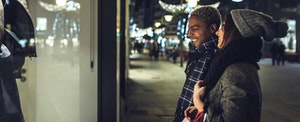 A young man and woman smile while looking into a store window, with holiday lights in the background.