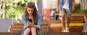 Young woman sitting on steps in a marketplace, looking purposefully at the screen of her smartphone in her hands