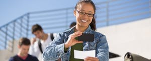 Happy young Asian-American woman using her smartphone to deposit her income by snapping a picture of her paycheck.
