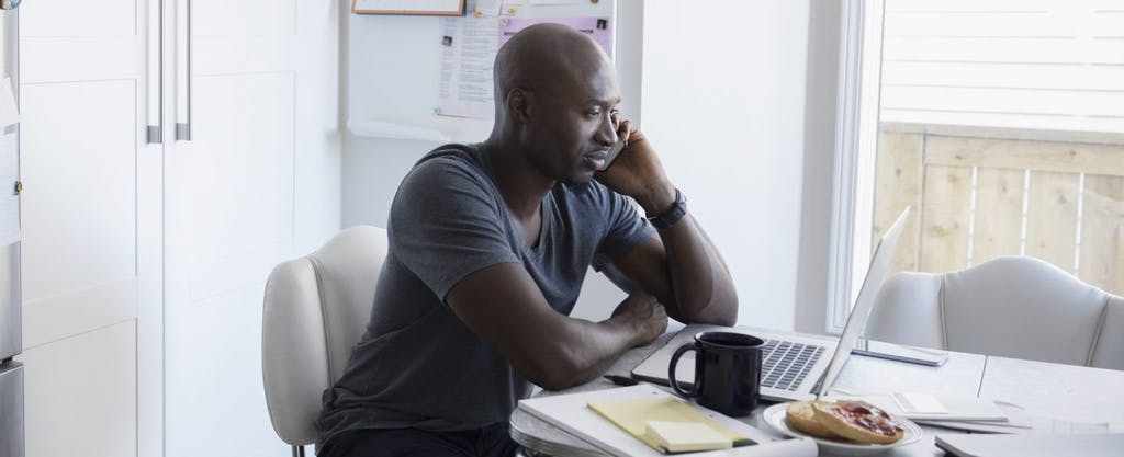 Young man calling the IRS phone number while sitting at his kitchen table and looking at a laptop.