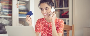 Young woman at home, looking at her computer while talking on the phone to find the best credit card.