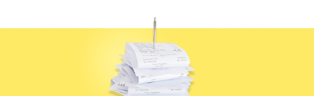 Self-employment taxes, represented by a stack of receipts against a yellow background