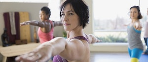A woman in a yoga class gazes ahead while holding the warrior II position.