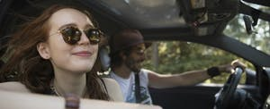 A couple drive a car after learning how insurance scores affect car insurance rates