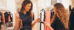 Woman paying via credit card at a clothing store.