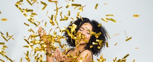 Young woman tossing confetti to celebrate the New Year and her financial New Year's resolutions