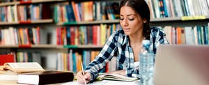Student studies with her college textbooks
