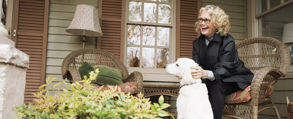 Senior woman sitting on porch rocking chair with dog
