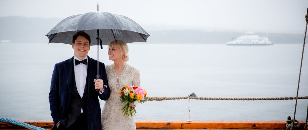 A smiling bride and groom stand outside on a deck under an umbrella on a rainy day.