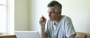 A man with gray hair holds a pen and studies his laptop.
