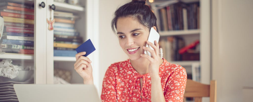 Credit card in hand, young woman works at home.