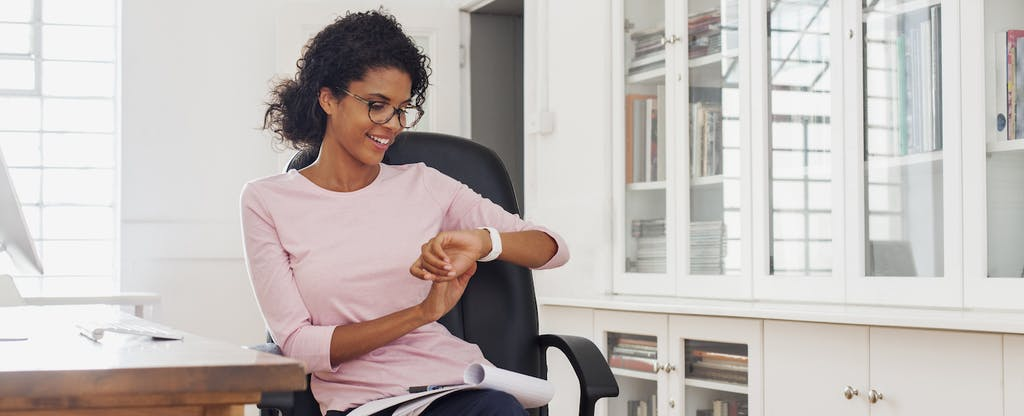 Young woman smiles as she checks her wristwatch in her home office, wondering how the age of her credit history impacts her credit scores,