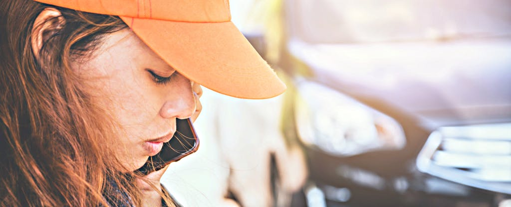 A young woman calls a friend to see if car repossession can hurt credit.