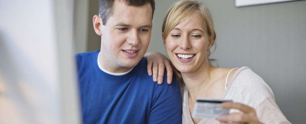 Couple using credit card to make an online purchase