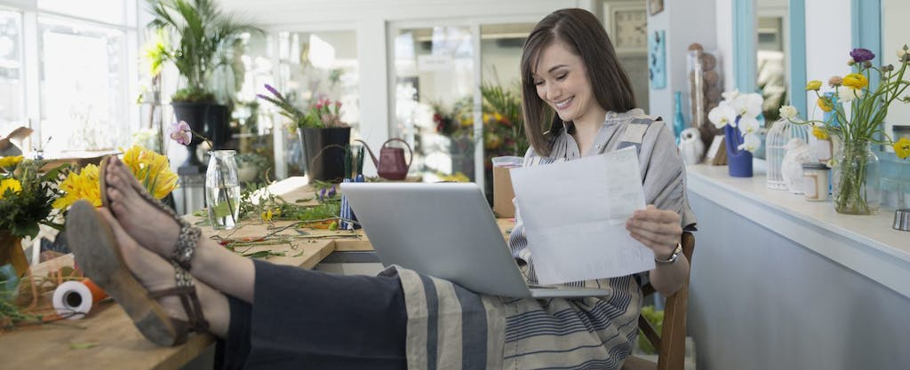 Confident young woman, feet up on desk, laptop on lap, smiling because she knows how to use Credit Karma Tax to do her taxes for free.