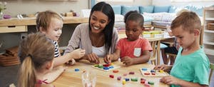 Smiling young teacher teaching children about letters and shapes in daycare.