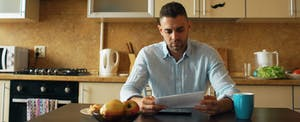 Worried young man sitting at his kitchen table and reading a letter from the IRS.