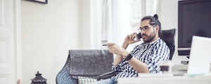 Young man at home with his feet up on the couch, calling his bank about an overdraft fee.