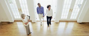 Mature realtor showing couple interior of house and explaining mortgage options