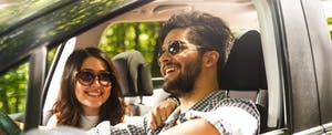 Young couple with sunglasses on, in a vehicle on a sunny day. View is through the driver's window, where a male is behind the wheel.