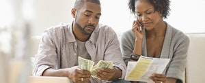 Young couple looking at their bills and struggling financially, wondering who to ask for help.