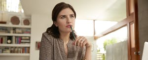 Pensive female working at desk in home office