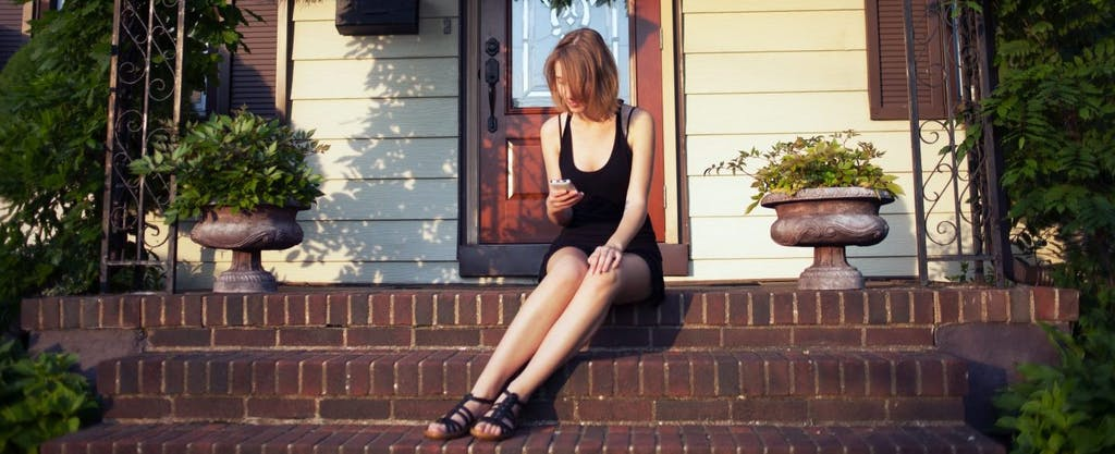Young woman sitting on the front porch of her home, using her mobile phone to look up what is a tax lien.