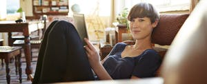 Young woman relaxing on couch at home, making notes and confident about her rights as a taxpayer.