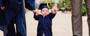 Close up of cute baby in blue graduation cap and gown, holding hands with mom and dad.