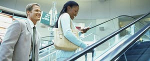 Business man and woman riding an escalator upward, while the woman reads about how tax brackets work on her mobile phone.