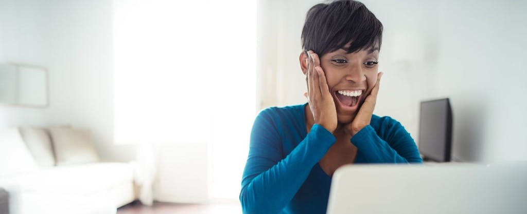 Young black woman, hands on cheeks and smiling, as she checks her laptop to discover if she has an unclaimed tax refund waiting for her.