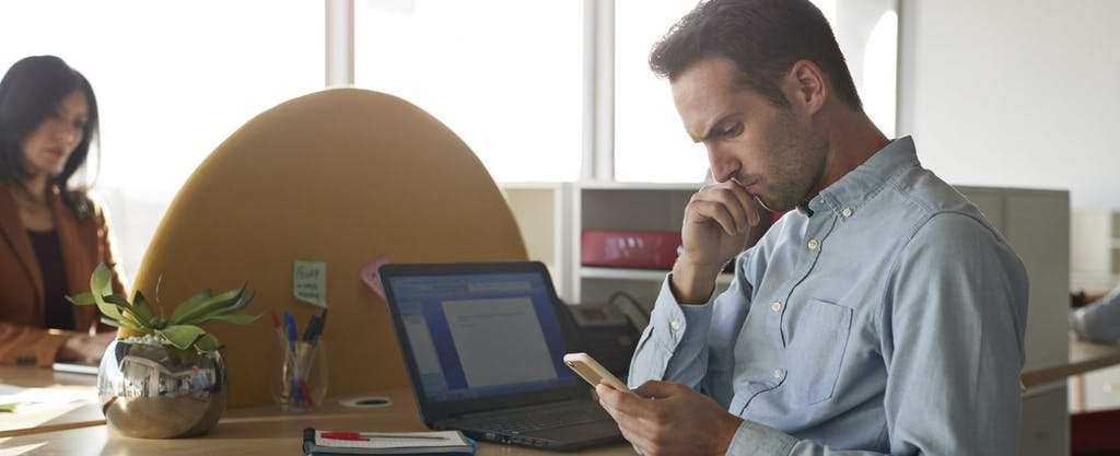 Businessman sitting at his desk, wondering if tax debt relief could help him.
