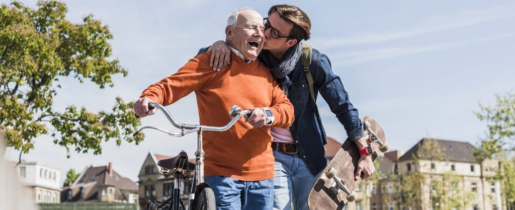 Adult grandson kissing his happy grandfather on the cheek while helping him ride a bike in the city.