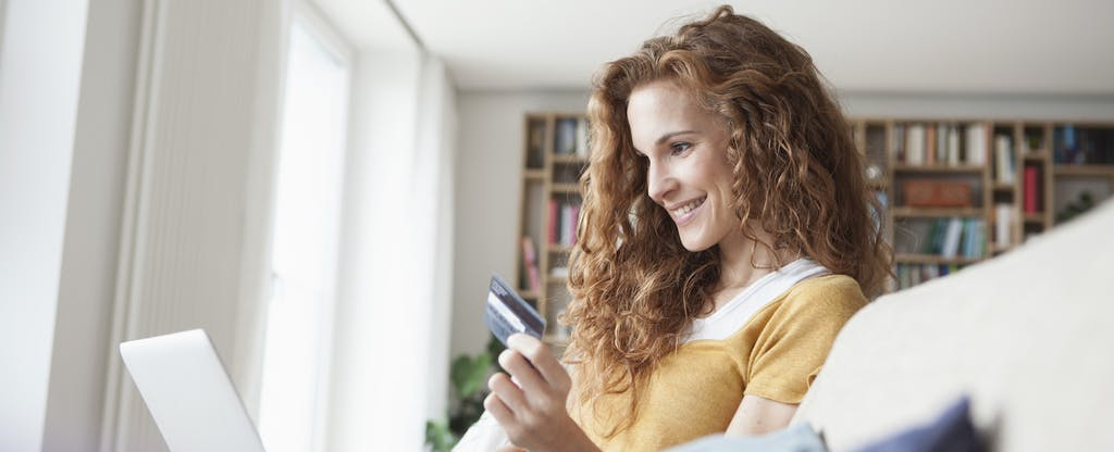 Young red-headed woman with long hair holding a PayPal Prepaid Mastercard in her left hand, laptop on her lap