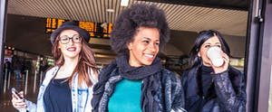 Three young women exiting an airport or train station, cellphones or coffee in hand