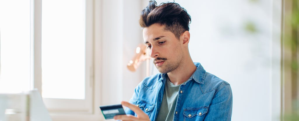 Young male looking at his credit card in a sunny room, looking worried and wondering what a fraud alert is.