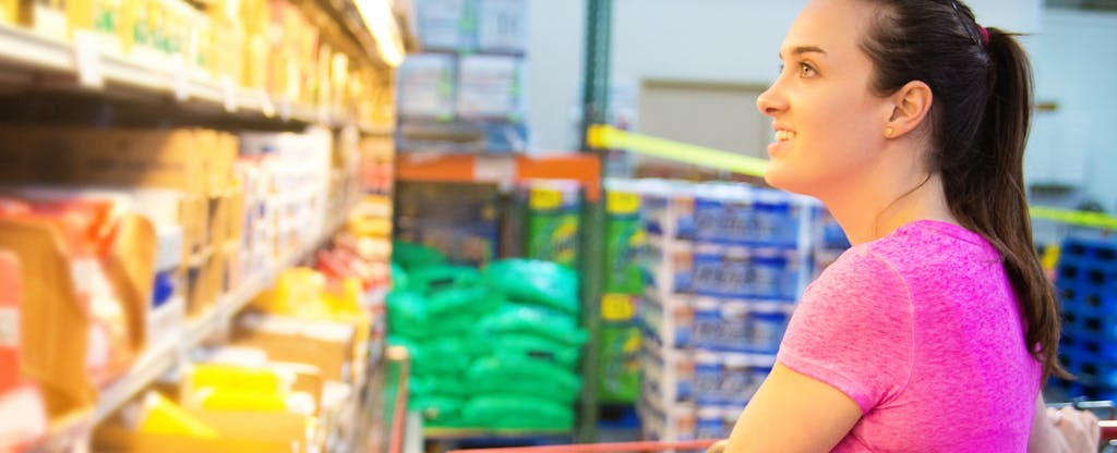 Young woman in front of refrigeration case with cheese and dairy, shopping in a warehouse-style grocery store.