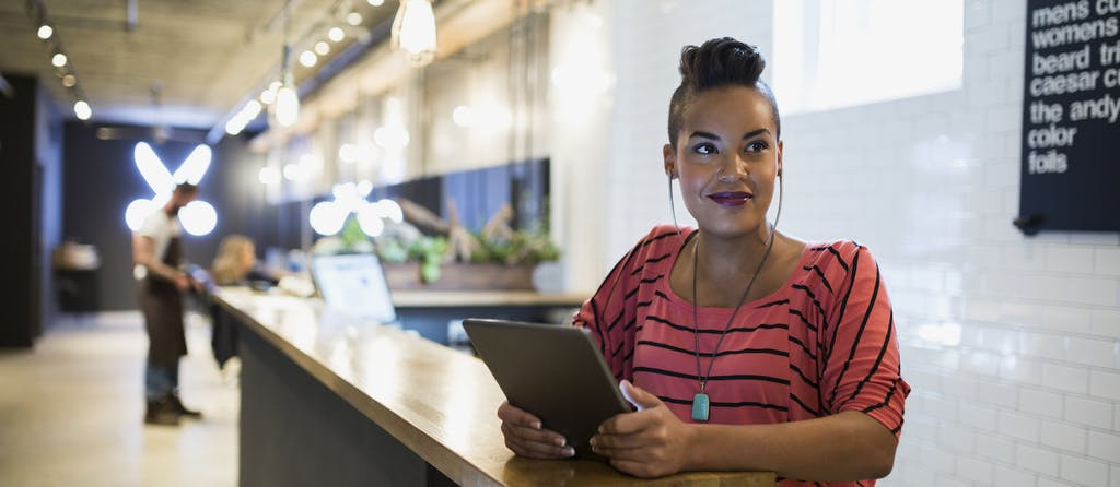 Hairstylist business owner with digital tablet in hair salon