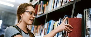 Happy young woman removing a book from a shelf in a college library