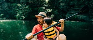 Father and his little girl paddling a packraft together on a river in a tropical environment