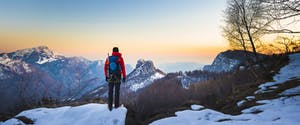Man in winter gear and backpack on a small Alaskan cliff, looking out at the sun setting over the mountains