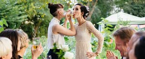 Brides link arms to drink champagne in celebration of their marriage.