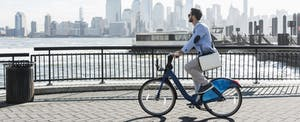 Young businessman biking to work from one state to another, city skyline in the background.