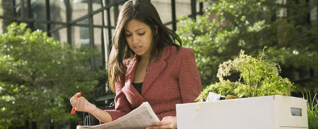 Young unemployed business woman sitting on a park bench, reading the help wanted ads with a box of her office possessions beside her.
